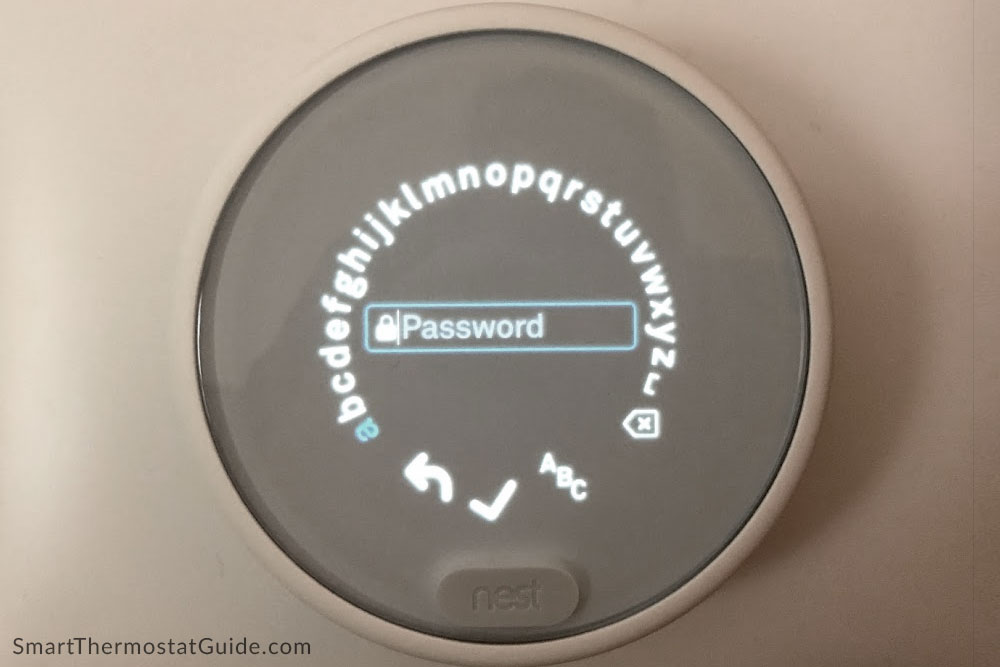 """Photo of Nest Thermostat E on """"enter WiFi password"""" screen. Each letter must be cycled to and """"clicked"""" on using the twist ring."""